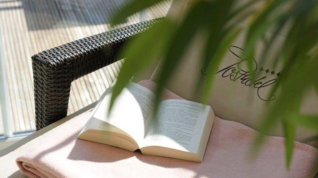 Buch liegt auf einer Sonnenliege
