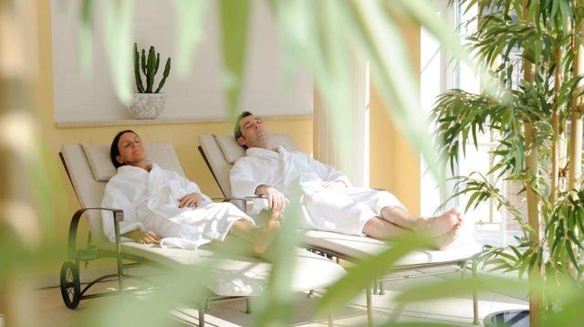Zwei Personen entspannen im Bademantel auf der Liege